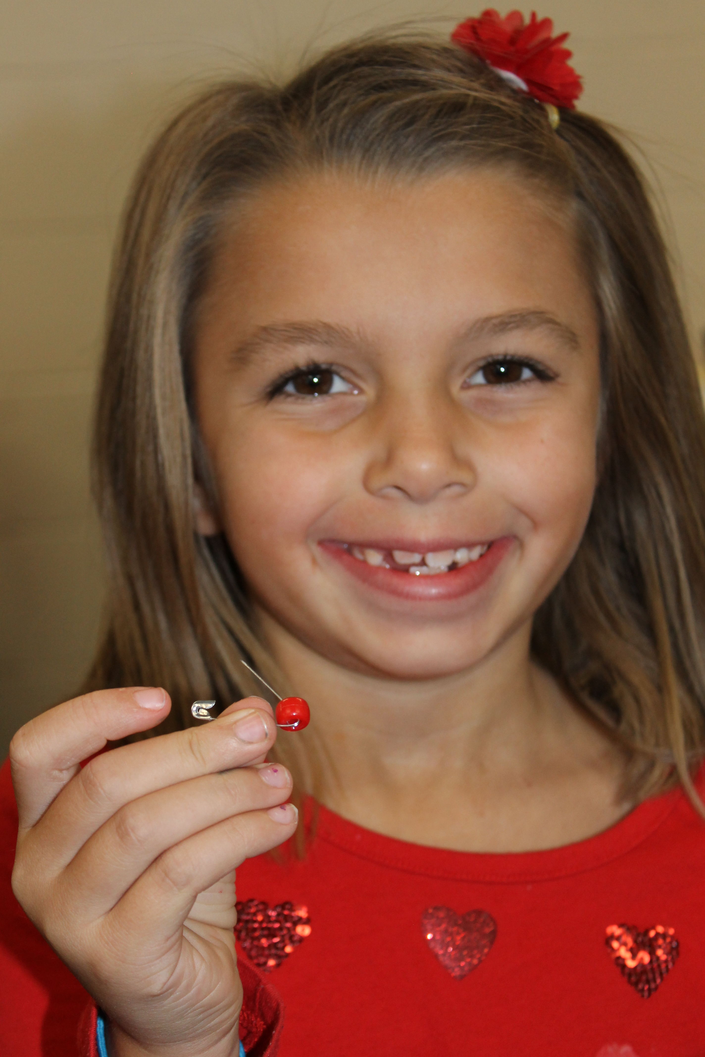 girl making a red ribbon bead pin