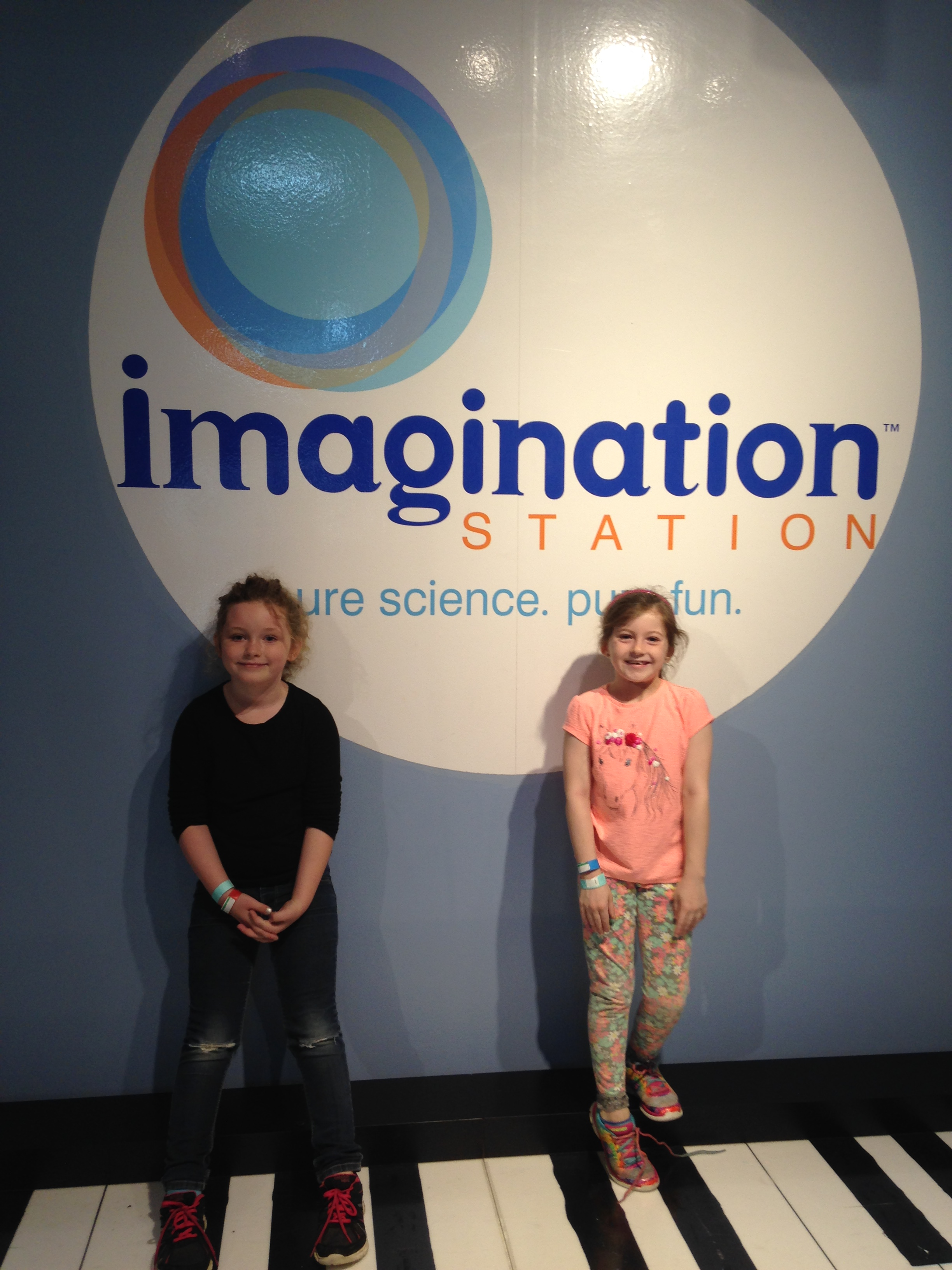 Girls in front of sign for Imagination Station